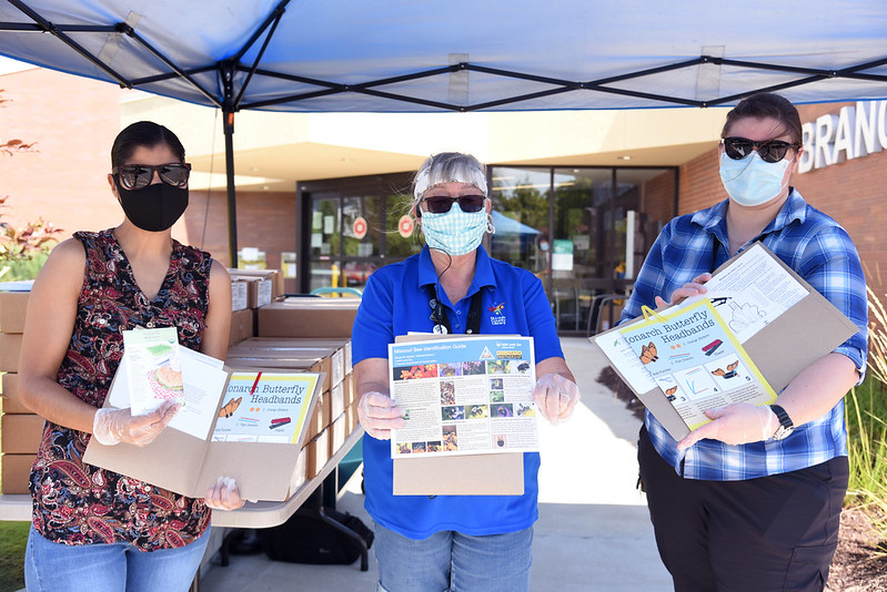Photo of three masked librarians each with learning kits in front of a library branch