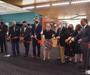 men and women standing in a line cutting a red ribbon