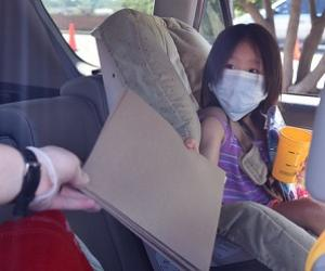 girl in car seat being handed a brown folder