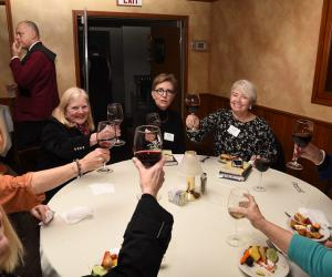 women raising a glass of wine around a table